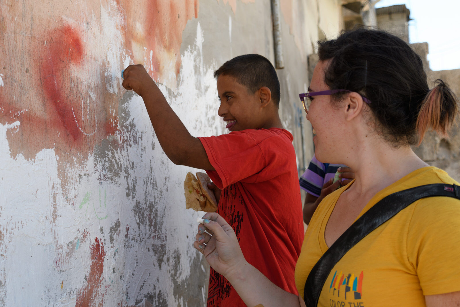 Betty draws on a wall with a child in Jerash refugee camp.