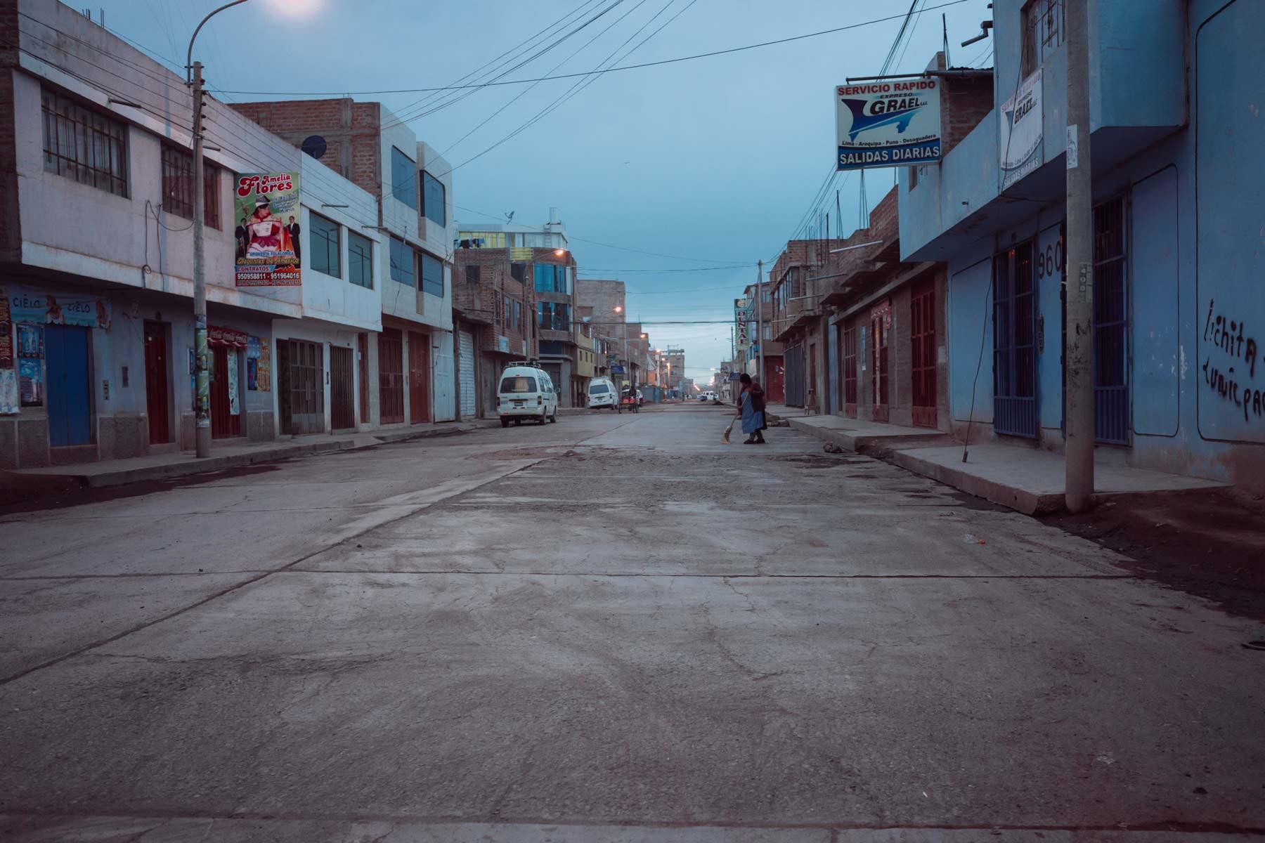 A woman sweeps an empty street as dawn breaks in Juliaca.