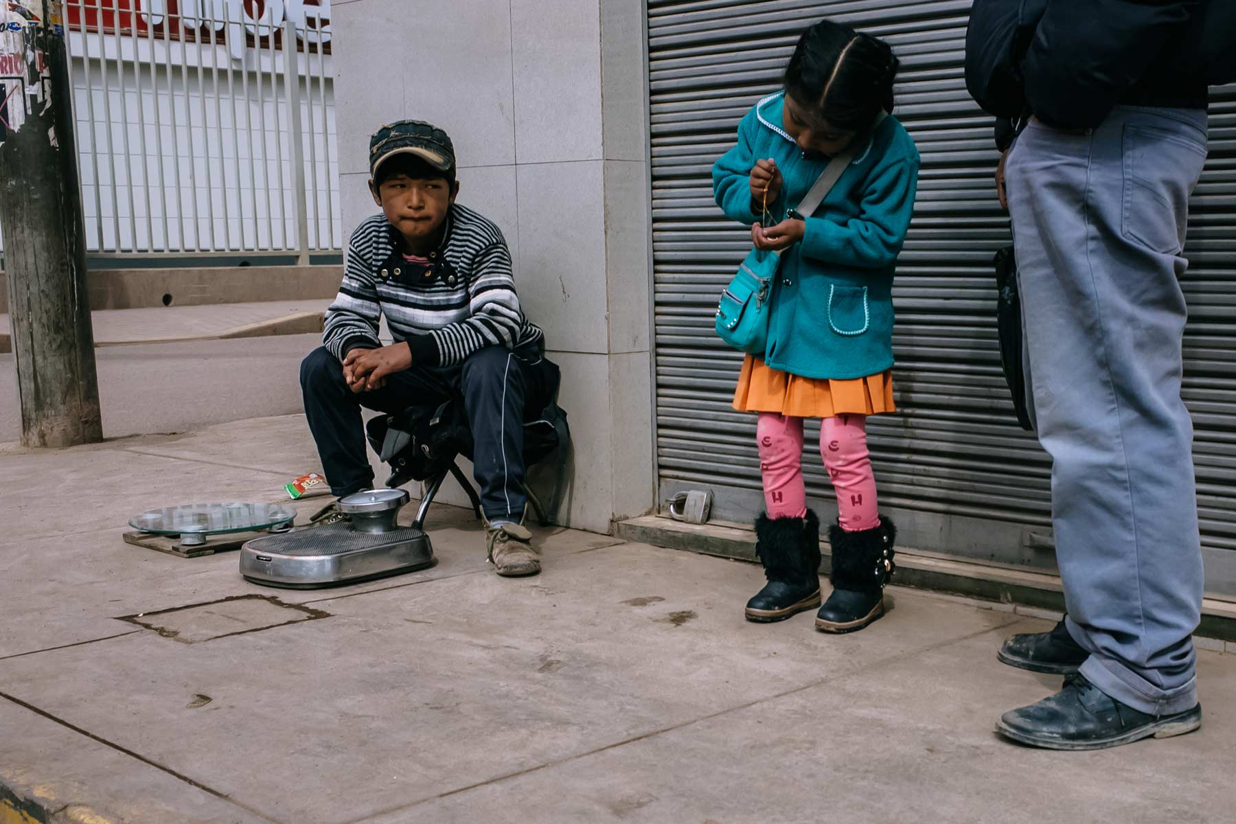 A working boy stares at a girl waiting to cross the street playing with a gold necklace in Juliaca.