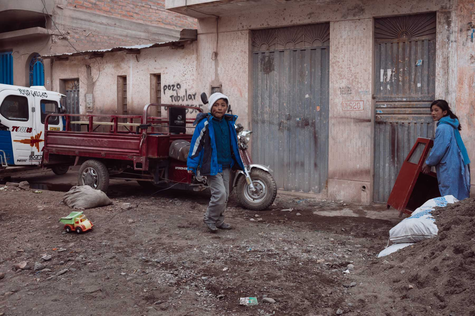 Two children playing with a toy dump truck in a residential area in Juliaca.