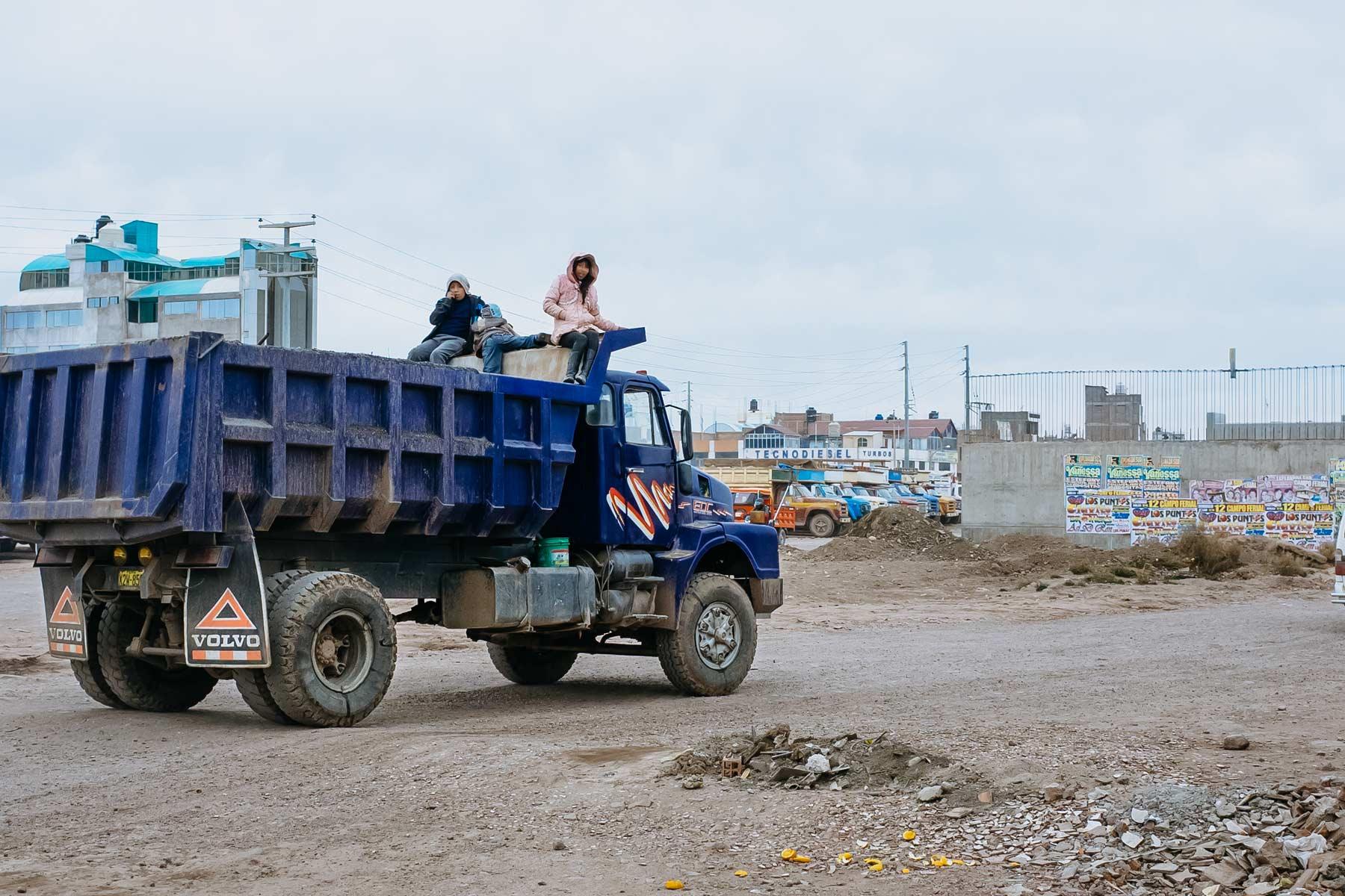 Three children riding on the back of a mining dump truck in Juliaca.