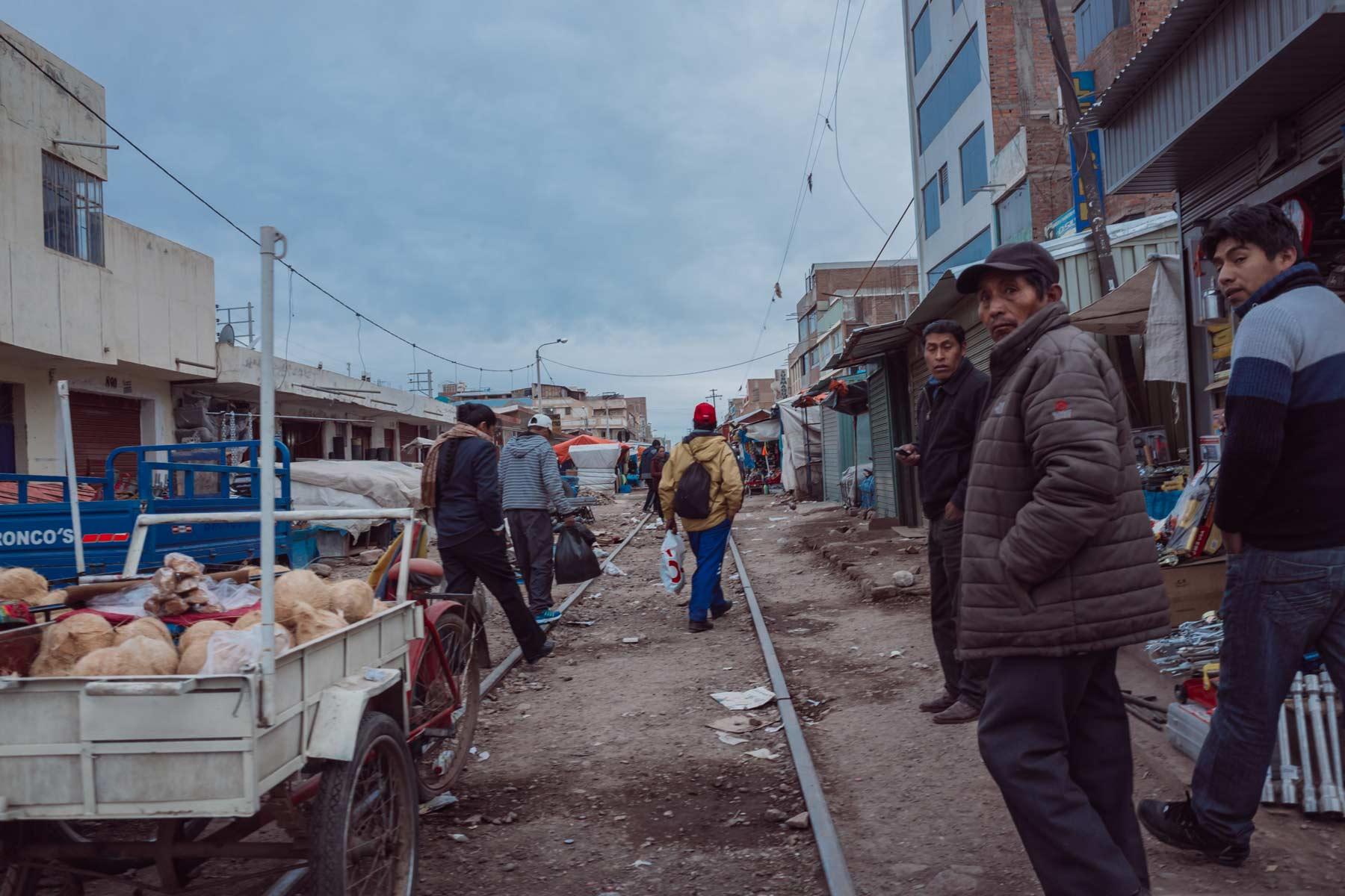Men walk to work through an outdoor market along Peru's railroad in Juliaca.