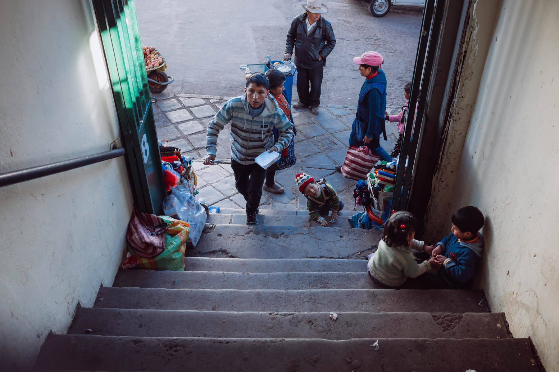 A young boy quickly ascends the steps of a local meat market in Cusco.