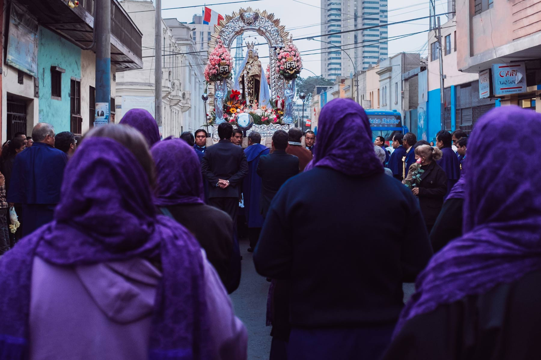 The procession of the Virgin Mary takes place in a small neighborhood in Lima.