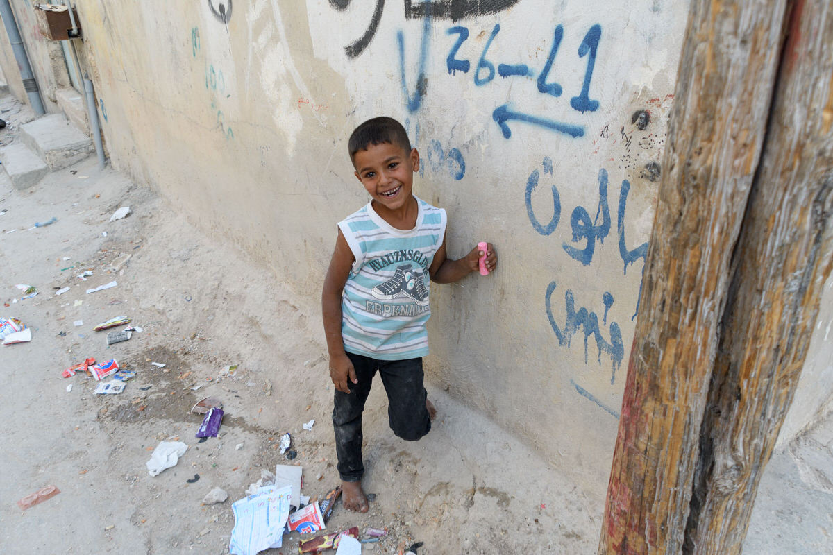 A happy child holding his new stick of sidewalk chalk in Jerash refugee camp.