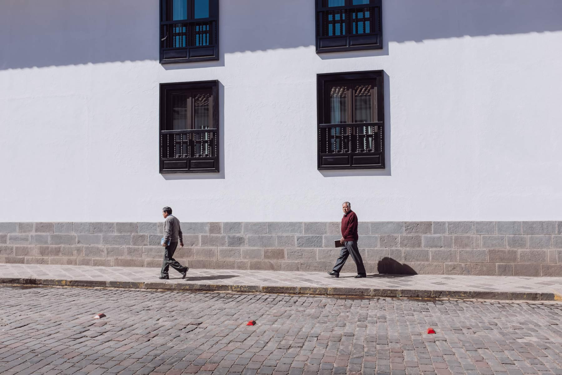 Two men pass in front of a luxury hotel in Cusco.