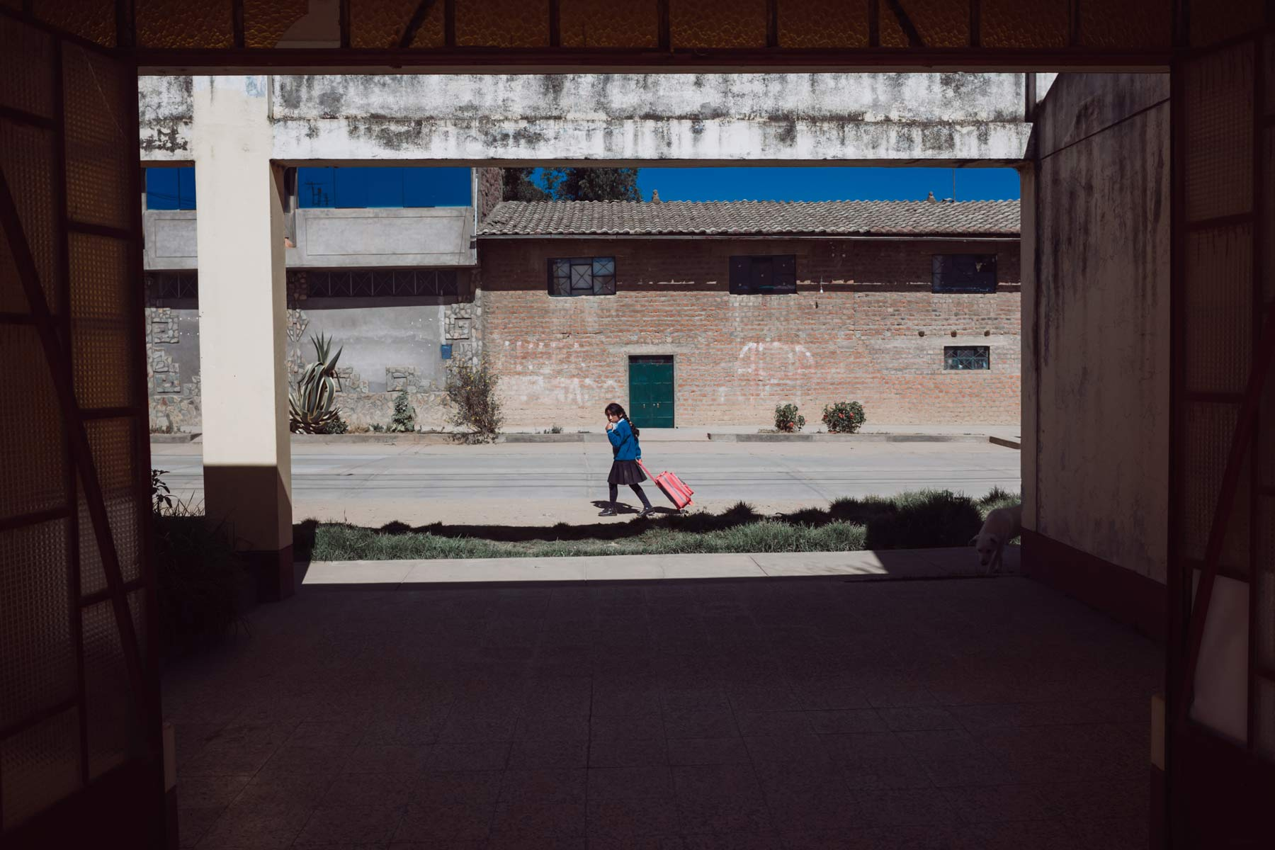 A school girl walking home crosses a large entryway in Hualhuas.