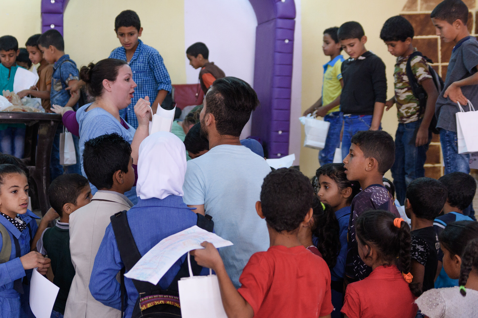 Chelsea and Mahmud distribute bags to eager children from Jerash refugee camp.