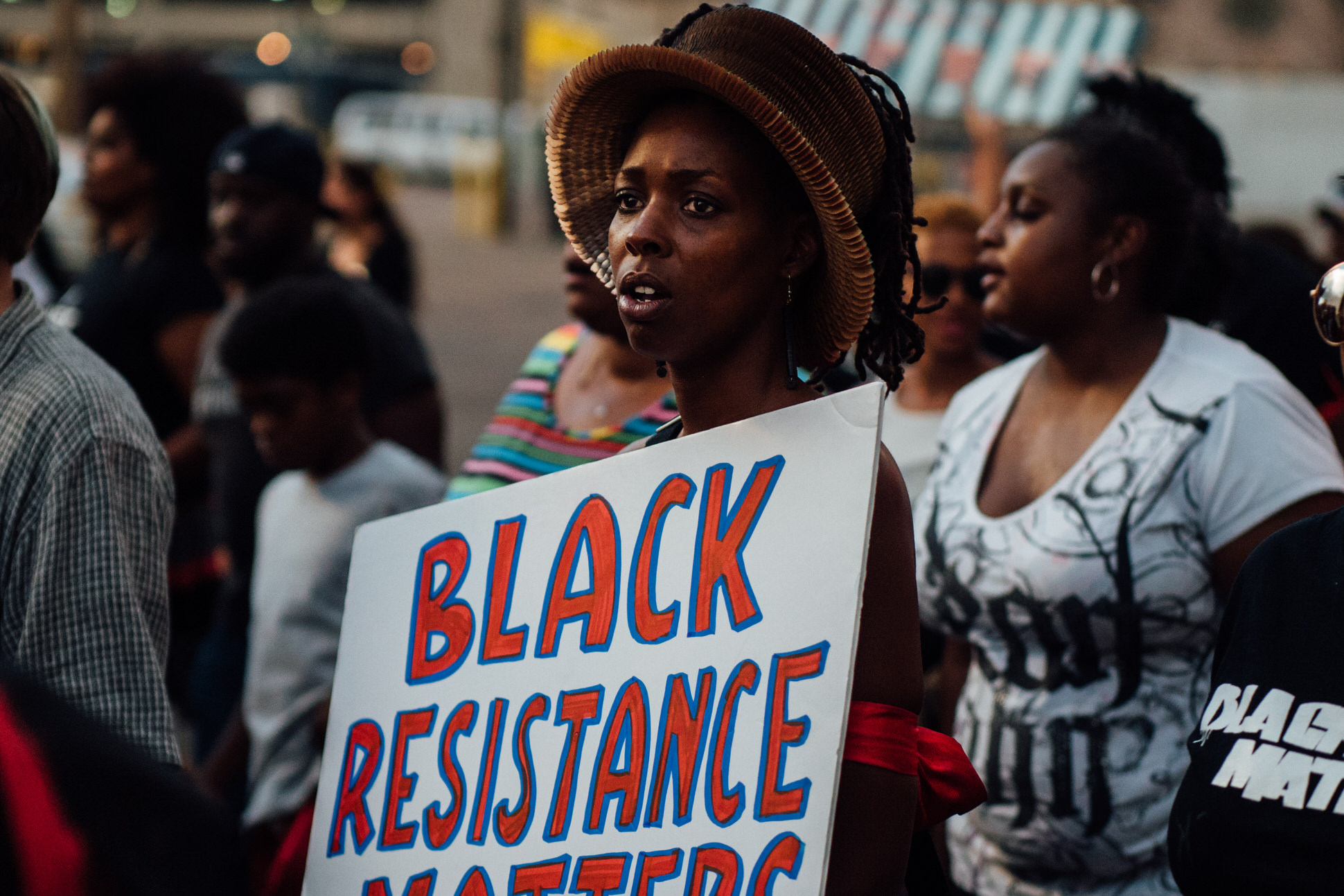 """A participant of the BLM 5280 march holds a sign that reads """"Black resistance Matters""""."""